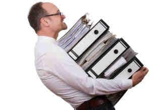 Overworked man carrying files