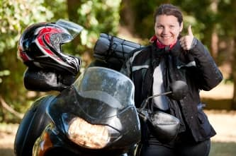 Woman on motorcycle giving thumbs up