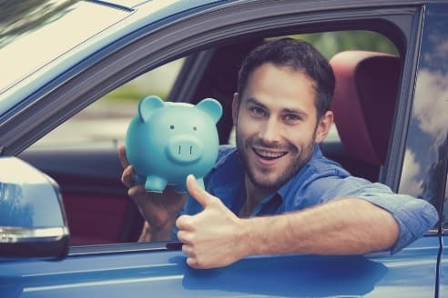 Happy driver in car with piggybank